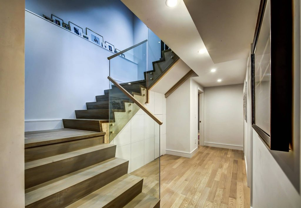 basement-staircase-with-glass-railings-and-baseboard-trim-interior-designer-oakville