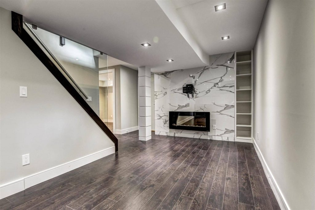 custom-basement-with-build-in-fireplace-and-baseboard-trim-basement-renovations-oakville