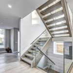 custom-staircase-with-glass-rialings-and-wooden-wall-decor-custom-home-builder