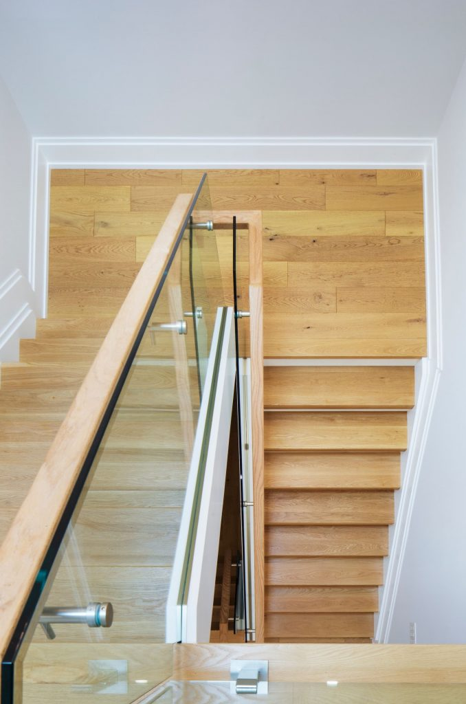 interior-staircase-with-wooden-stairs-and-glass-railings-full-house-renovations