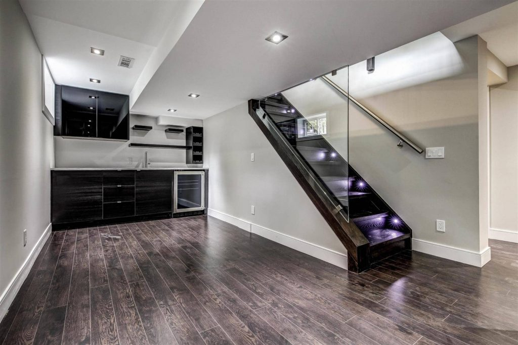 luxury-basement-with-small-kitchen-and-backlit-staircase-basement-renovations-hamilton