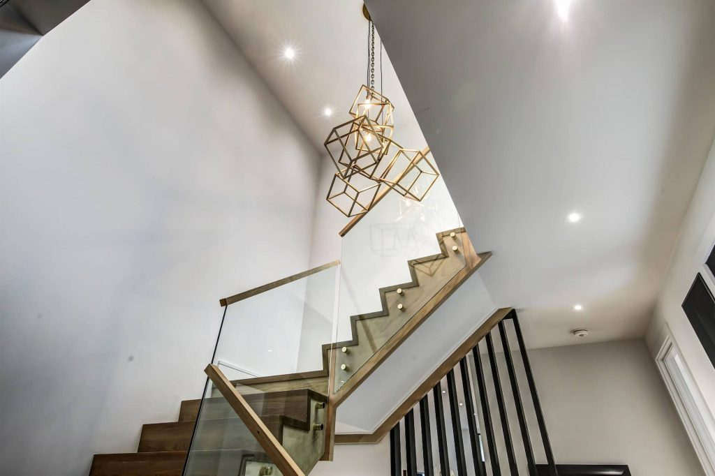 modern-staircase-with-glass-railings-and-custom-chandelier-interior-design-company-Toronto-and-GTA